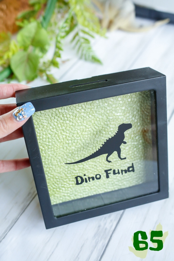 A shadow box bank with a black dinosaur image and the words dino fund on it