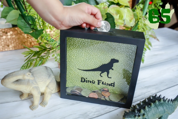 A child's hand adding coins to a dino fund shadow box bank with dinosaur toys and greenery