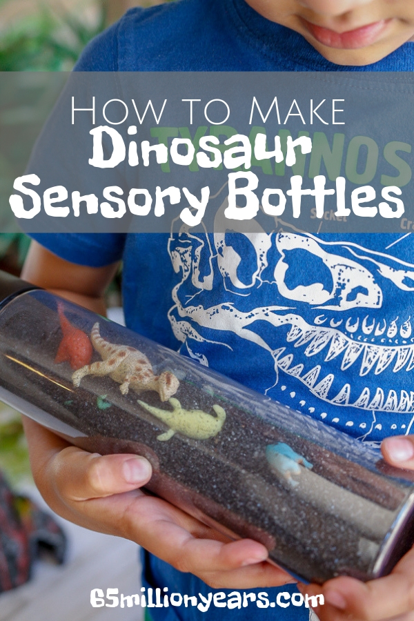 A child holding a sensory bottle filled with miniature dinosaur toys and sand with the text how to make dinosaur sensory bottles